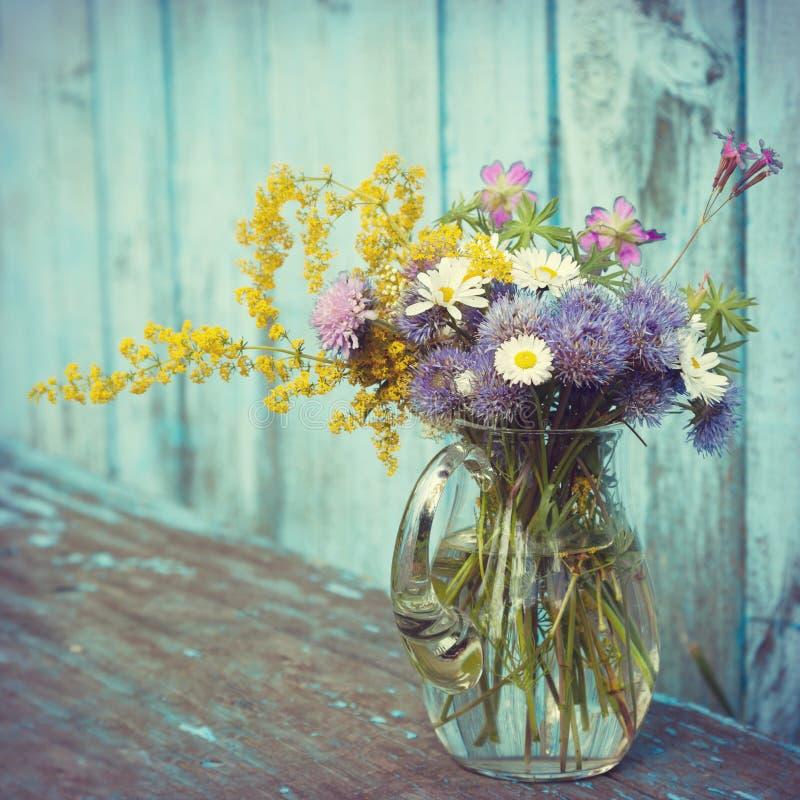 Bukett av trädgårdblommor och läkaörter i den glass tillbringaren royaltyfri fotografi