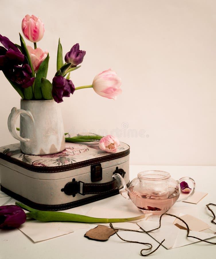 Bukett av tulpan och en gammal resväska på tabellen, Provence, sjaskig stil royaltyfria bilder