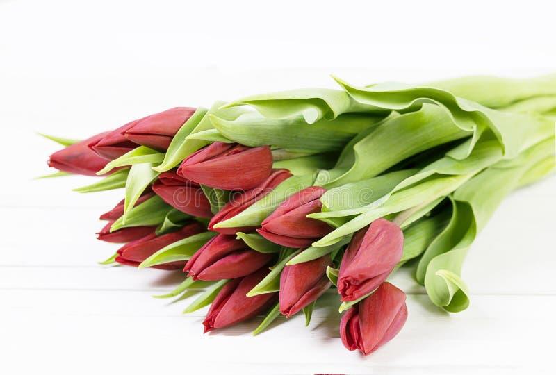 Bukett av tulpan på en vit tabell Röda tulpan på vita bräden royaltyfria foton
