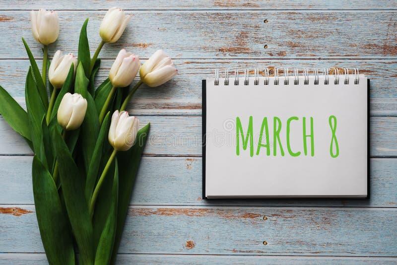 Bukett av vita blommor av tulpan på bakgrunden av blåa bräden med en anteckningsbok med att märka mars 8 royaltyfri bild