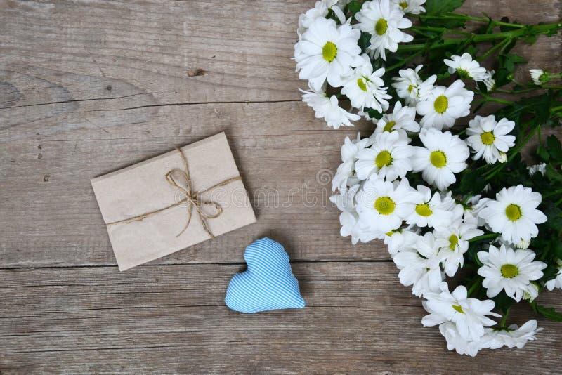 Bukett av vita krysantemum med kuvert- och blåtthjärta på trä fotografering för bildbyråer