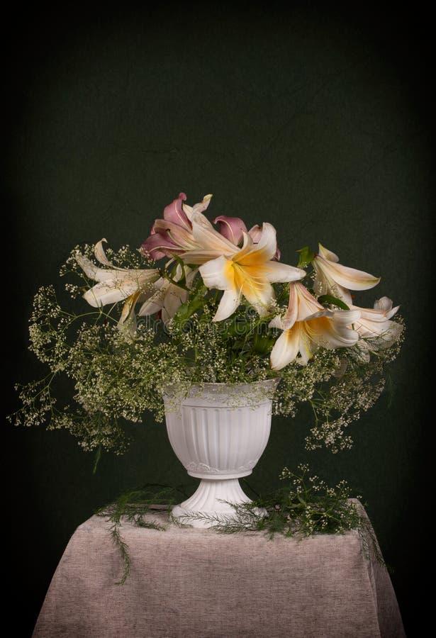 Bukett av vita liljor i en gammal vas arkivbilder