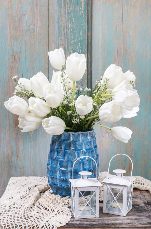 Bukett av vita tulpan i blå keramisk vas royaltyfria foton