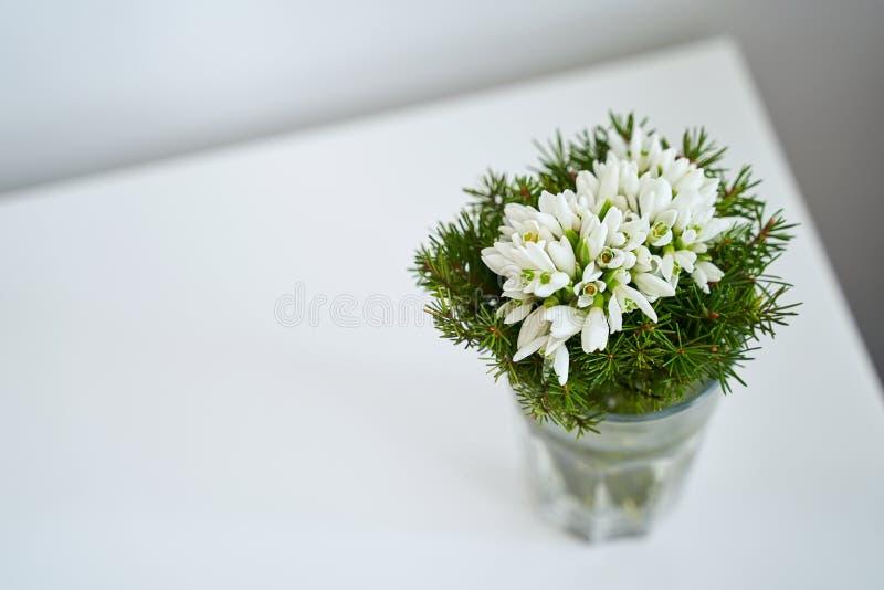 Bukett för blomma för vårferiesnödroppe i en exponeringsglasvas hemma arkivfoto