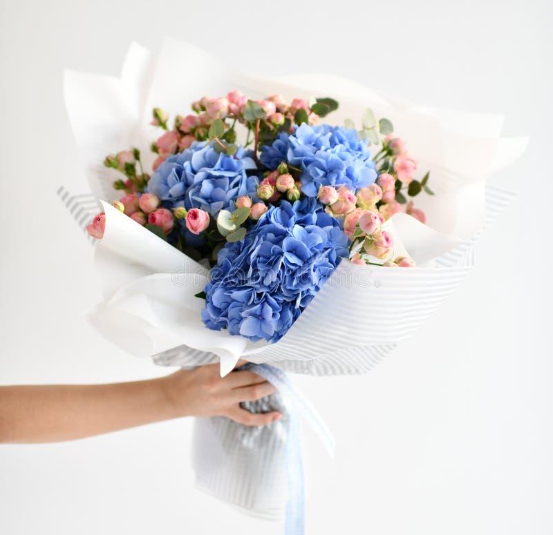 Bukett för kvinnahandhåll av blåa vanlig hortensiablommor och rosa rosor royaltyfri fotografi