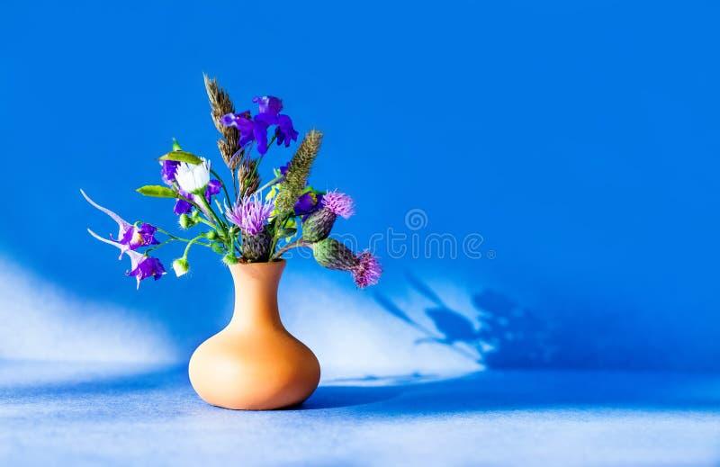 Bukett för lösa blommor, brun leravas på blå bakgrund Foto för stilleben för solig dag för sommartid floristic grunt royaltyfria foton