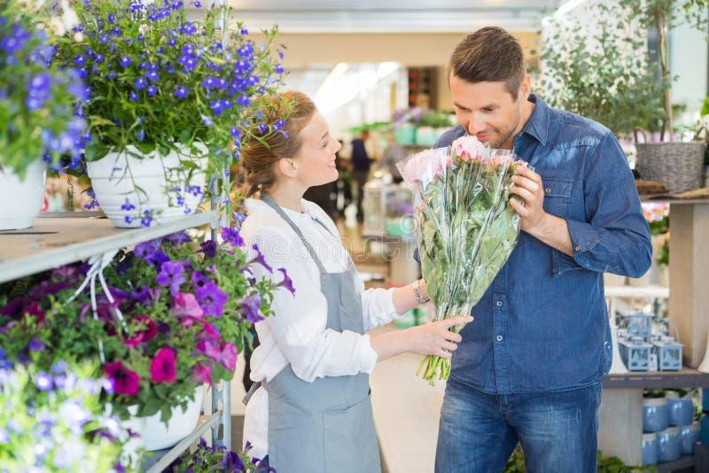 Bukett för ny blomma för blomsterhandlareGiving Customer To lukt royaltyfria foton