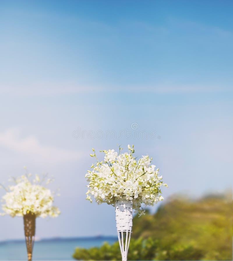 Bukett för vit blomma på bambuvasgarneringen i mötesplatsen för strandbröllop, oskarp bakgrund arkivfoto
