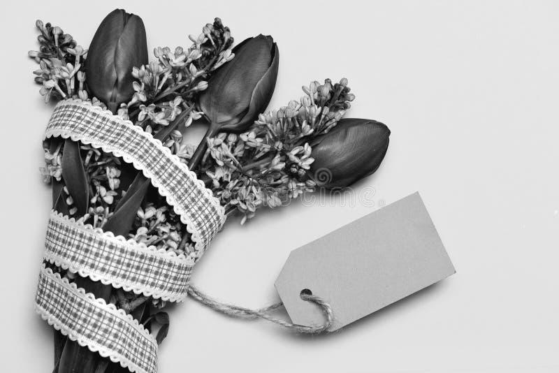 Bukett med anmärkningskortet: tulpan och lila med den purpurfärgade etiketten arkivbild