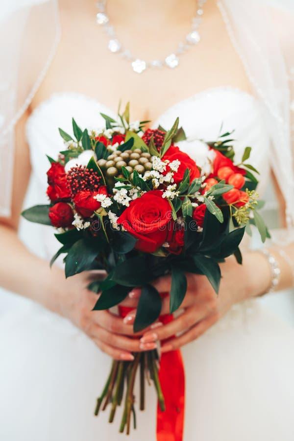 Bukett med röda rosor i händerna av bruden arkivfoton