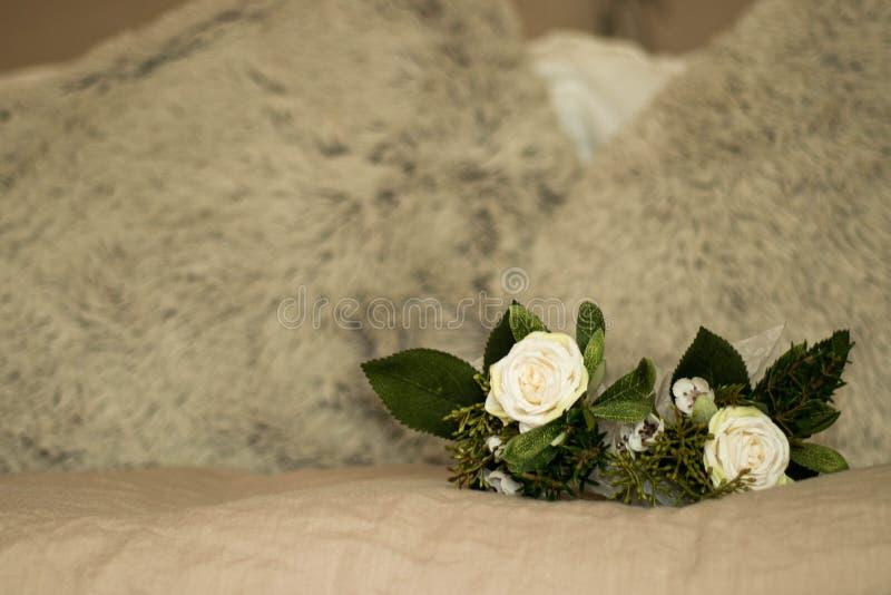 Bukettdetalj för vita rosor överst av beige säng med fluffiga kuddar arkivfoto