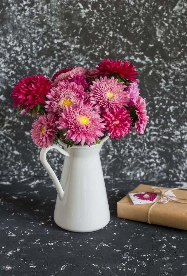 Buketten av blommor i en vit tillbringare och den handgjorda gåvan i hantverk skyler över brister royaltyfri fotografi
