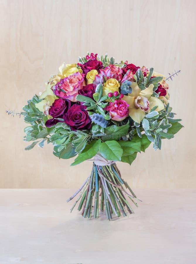 Buketten av blommor, mång--färgade rosor med gröna sidor står royaltyfria foton