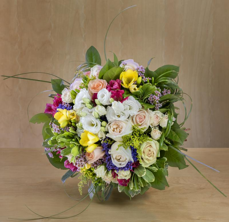 Buketten av blommor, mång--färgade rosor med gröna sidor står royaltyfri foto