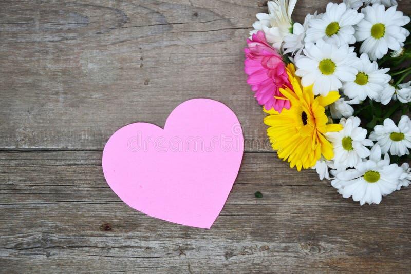 Buketten av blommor med rosa färger skyler över brister hjärta på trä arkivbild