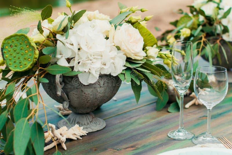 Buketten av blommor och grönska är på brölloptabellen royaltyfri foto