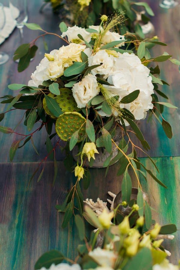 Buketten av blommor och grönska är på brölloptabellen arkivbilder