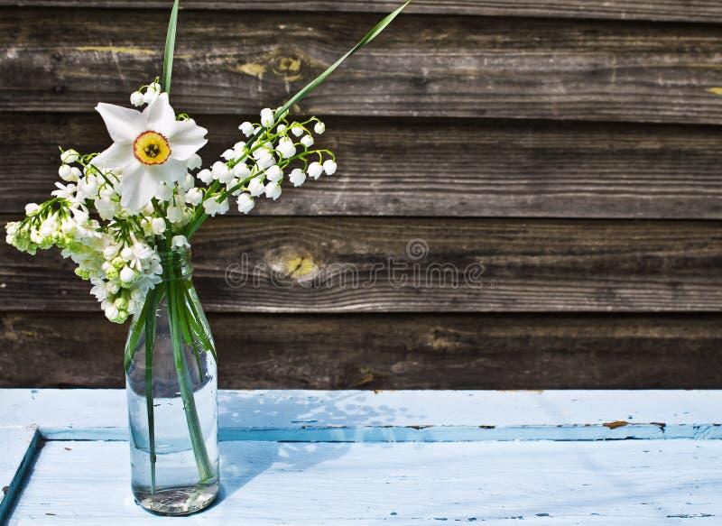 Buketten av den vita våren blommar i en flaska arkivfoton