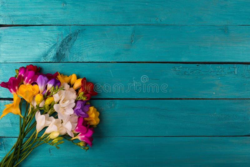 Buketten av freesia blommar på en träbakgrund royaltyfri foto