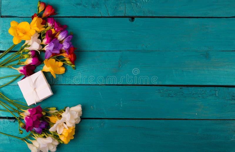Buketten av freesia blommar på en träbakgrund royaltyfri fotografi