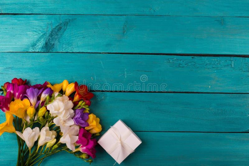 Buketten av freesia blommar på en träbakgrund royaltyfria foton