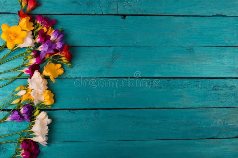 Buketten av freesia blommar på en träbakgrund royaltyfria bilder