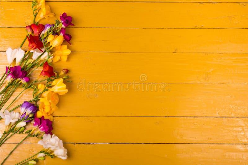 Buketten av freesia blommar på en träbakgrund arkivbilder