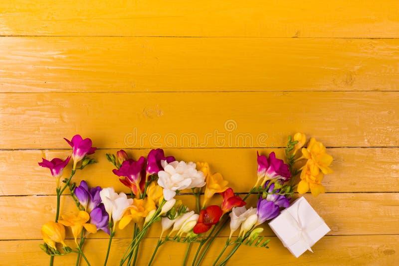 Buketten av freesia blommar på en träbakgrund arkivfoton