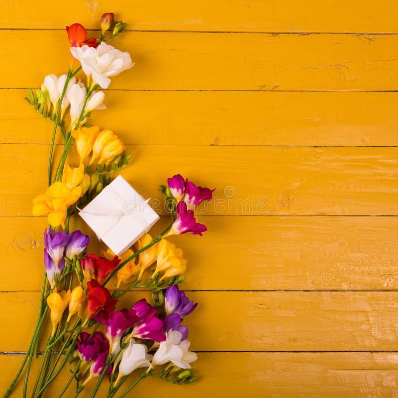 Buketten av freesia blommar på en träbakgrund arkivfoto