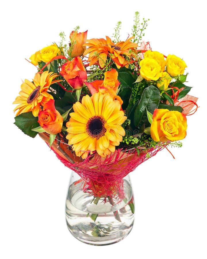 Buketten av gerberaen, rosor och annan blommar i den glass vasen arkivbild