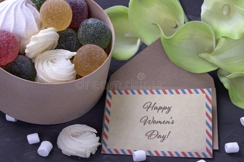 Buketten av gräsplangulingcallas med marshmallowmarmelad i en trärund ask och kuvertet på grå färger hårdnar bakgrund och lett royaltyfri bild
