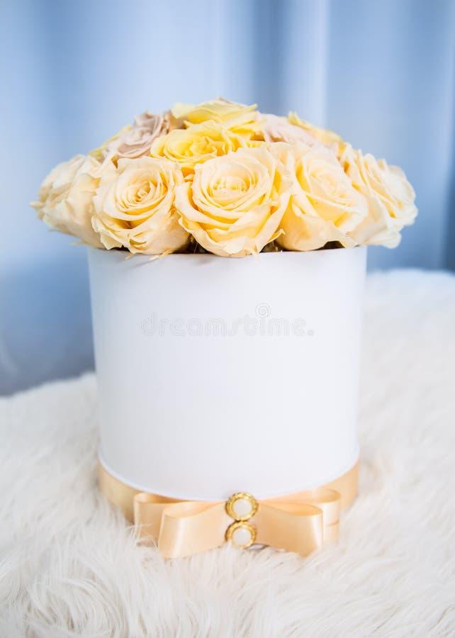 Buketten av guling blommar rosor i lyxig gåvaask royaltyfria bilder