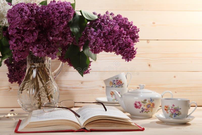 Buketten av lilor, öppnar boken, anblickar, tekannan och kopp te arkivbilder