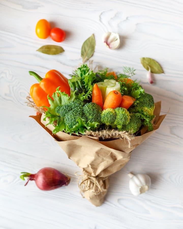 Buketten av nya grönsaker ligger på en vit trätabell Närliggande är en röd lök, tomater, vitlök, lagerblad ovanför sikt royaltyfri fotografi