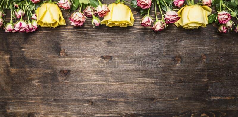 Buketten av rosor av olika sorter av blommor, gula rosor och rosa buskerosor gränsar, förlägger text på trälantlig backgro royaltyfria bilder