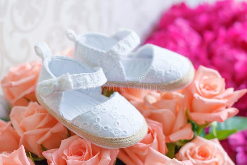Buketten av rosor och par av skor för ett nyfött behandla som ett barn royaltyfri bild