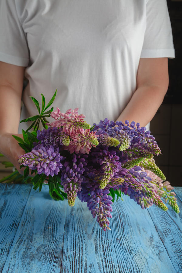 Buketten av sommar blommar i kvinnliga händer mot en träsurfa arkivfoton