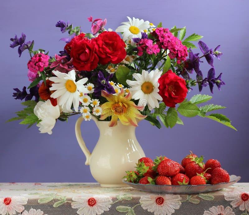 Buketten av trädgården blommar i en tillbringare och jordgubbar arkivfoto