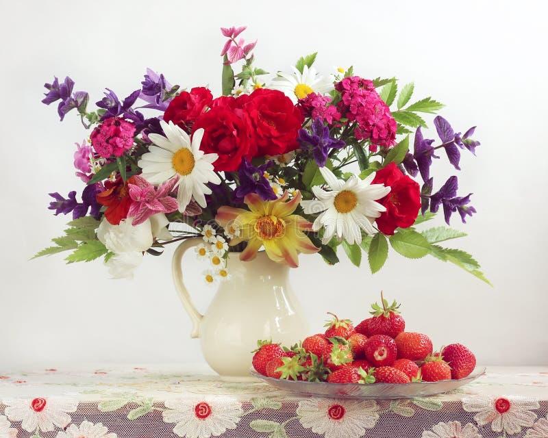 Buketten av trädgården blommar i en tillbringare och jordgubbar arkivbild