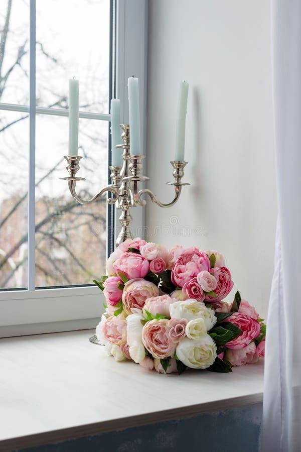 Buketten av vit och rosa färger blommar med stearinljus nära fönstret arkivbilder