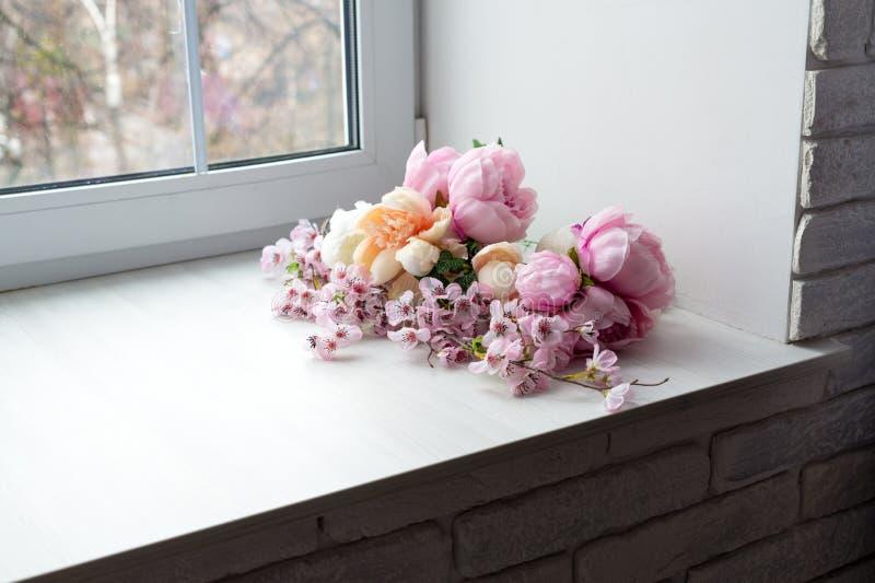 Buketten av vit och rosa färger blommar nära fönstret royaltyfria foton
