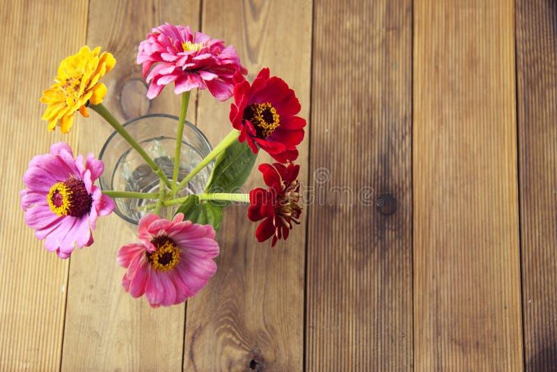 Buketten av zinniaen blommar över träbakgrund, bästa sikt royaltyfri foto