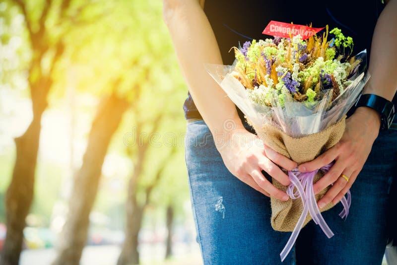 Buketten blommar lyckönskan i händerna av kvinnan royaltyfri fotografi
