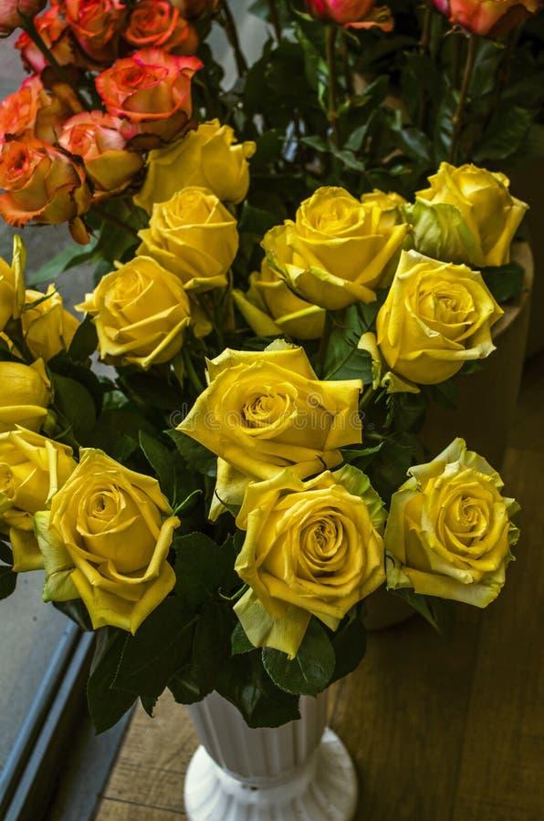 Buketten med stora gula rosor i en vit blomkruka vid fönstret i staden shoppar royaltyfri bild
