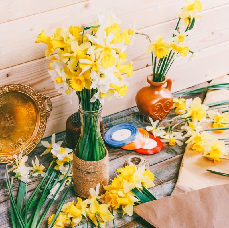 Buketter av gula påskliljor blommar i en vas och en kanna av Kraft papper och kulöra band med en härva av repet på en träta royaltyfri fotografi