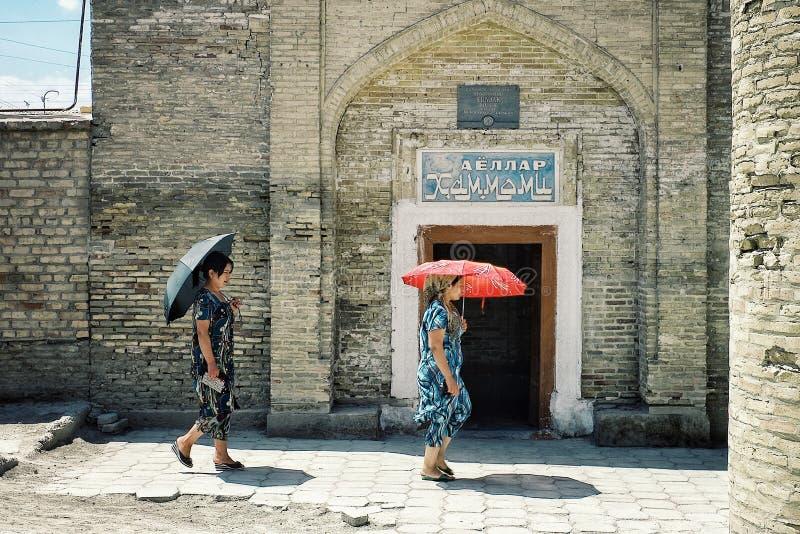 Bukhara/Uzbekistán - 5 de mayo de 2010: mujer que camina delante de una casa tradicional del baño en la ciudad emparedada históri foto de archivo