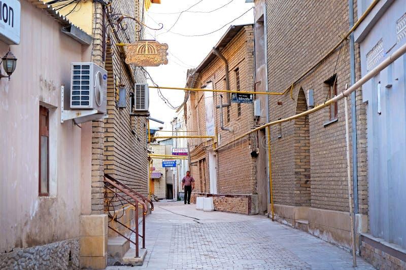 BUKHARA, UZBEKISTÁN - 1 de mayo de 2019 - pequeña calle con los edificios viejos y los hoteles acogedores en el viejo centro de c imagen de archivo