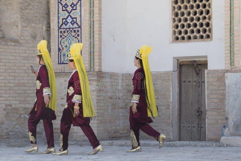 BUKHARA UZBEKISTAN - MAJ 25, 2018: Silke och kryddafestival 2018 Bukharian dansareflickor i lokal klänningdans royaltyfri bild