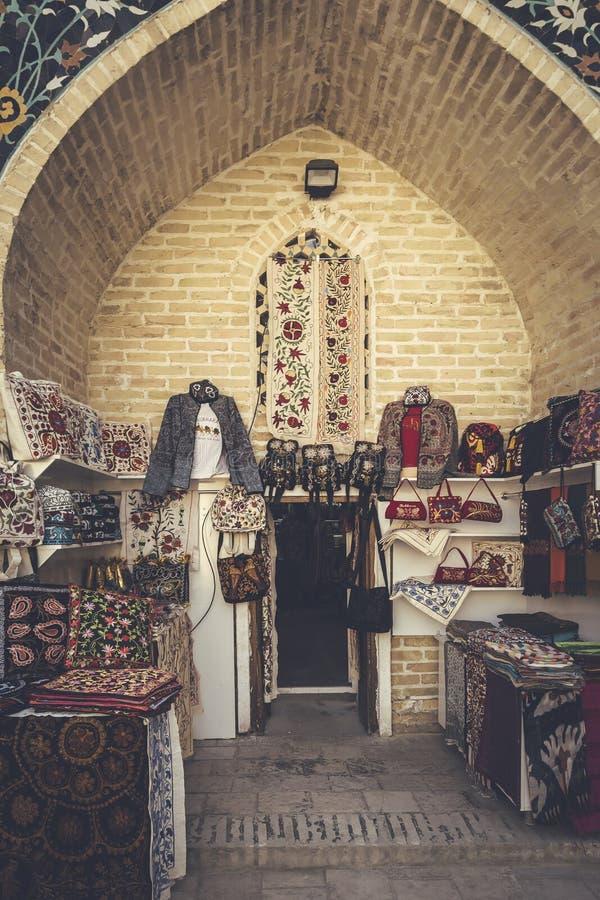 Bukhara Uzbekistan - mars 13, 2019: Den utomhus- gatan shoppar insidan av Nadir Divan-Begi Madrasah arkivbild