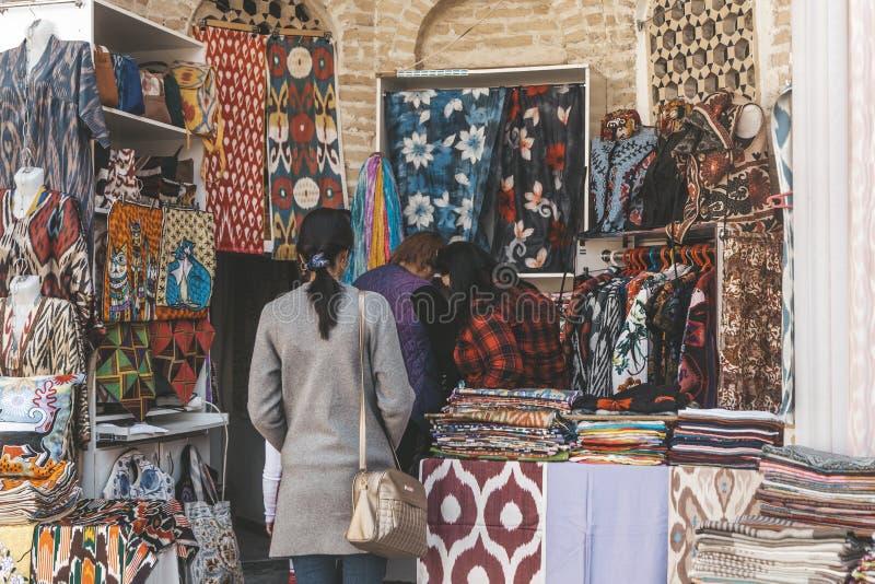 Bukhara Uzbekistan - mars 13, 2019: Den utomhus- gatan shoppar insidan av Nadir Divan-Begi Madrasah royaltyfri foto